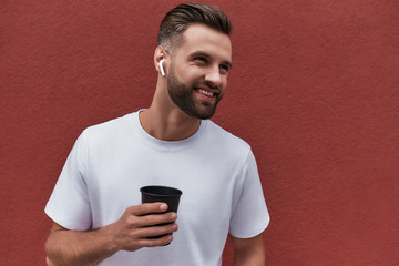 Wall Mural - Young and happy. Handsome bearded man in headphones holding cup of coffee and smiling while standing against red wall outdoors