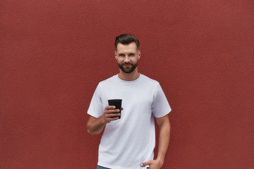 Wall Mural - Good time. Portrait of handsome man in casual clothes holding cup of coffee and looking at camera while standing against red wall outdoors