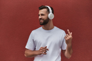 Wall Mural - I am cool. Portrait of happy handsome man in headphones listening to the music and smiling while standing against red wall outdoors