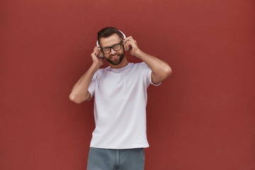 Wall Mural - Enjoying my favourite song. Portrait of handsome and cheerful man in eyeglasses wearing headphones and listening to the music while standing against red wall outdoors