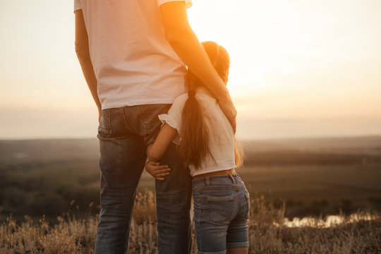 Happy father and daughter hugging while standing at countryside