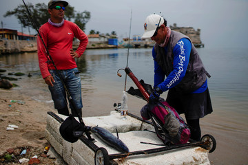 Fisherman Josue Prado chats with a friend after returning from the sea in his raft made out of foam in Cojimar