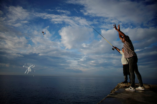 Fishermen throw inflated condoms carrying baited hooks for fishing at the seafront Malecon in Havana