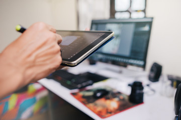 Photographer Works Editing Photo in a Tablet at a close up shot.