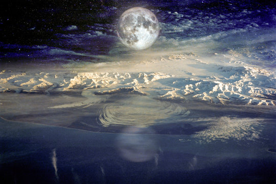 Snow covered mountains against blue sky with clouds and moon in winter at night. Arctic landscape with sea, snowy rocks, moonlight, reflection in water. Elements of this image furnished by NASA.