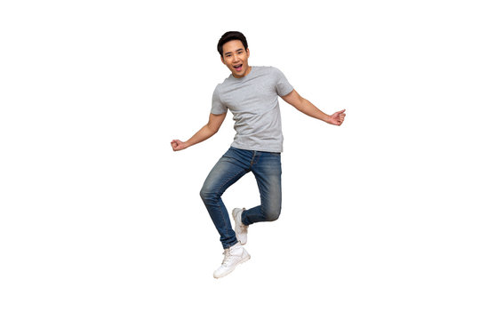 Excited Asian young man in gray t-shirt jumping while celebrating success isolated over white background, Full length portrait concept