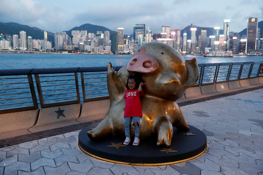 A girl poses for a picture at the bronze sculpture of McDull, an anthropomorphic pig cartoon character, along Tsim Sha Tsui's waterfront, at Hong Kong's Avenue of Stars