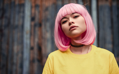 Pensive Asian woman with pink hair