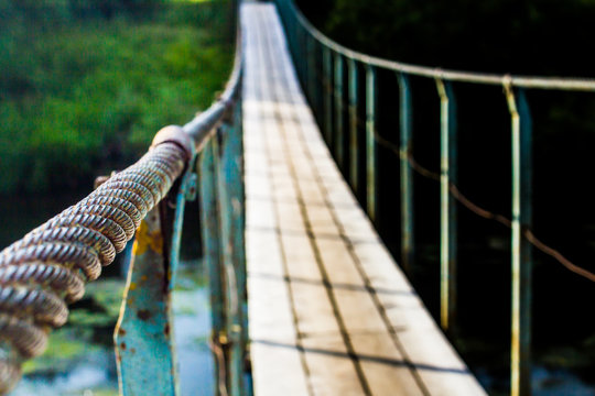 old suspension bridge over a small river in the forest in summer, bridge elements