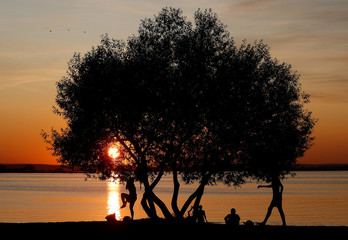 People enjoy sunset at a lake on the outskirts of Minsk