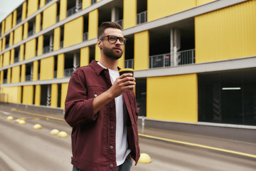Wall Mural - Great day. Handsome bearded man in casual wear and eyeglasses holding a disposable cup while walking through the city street