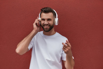 Wall Mural - My inspiration. Portrait of handsome man in headphones listening to the music and smiling while standing against red wall outdoors