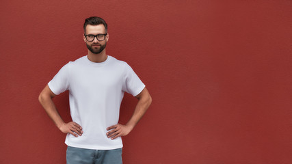Wall Mural - Young and handsome. Portrait of confident and attractive bearded man in eyeglasses keeping arms on his hips and looking at camera while standing against red wall outdoors