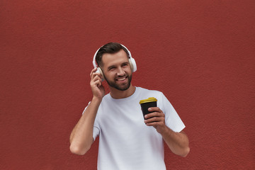 Wall Mural - Enjoying this day Portrait of happy handsome man in headphones listening to the music and drinking coffee while standing against red wall outdoors