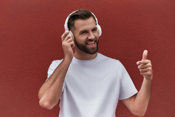 Wall Mural - I like this song Portrait of happy handsome man in headphones listening to the music and showing thumb up while standing against red wall outdoors