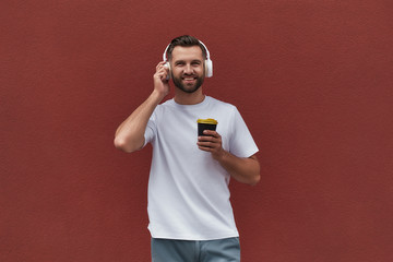 Wall Mural - I love my life Portrait of happy handsome man in headphones listening to the music and holding cup of coffee while standing against red wall outdoors