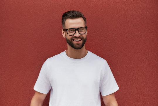 I am happy! Portrait of cheerful attractive bearded man in eyeglasses smiling and looking at camera while standing against red wall outdoors