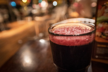 Shallow depth of focus on the froth in a glass of chicha morada served at a Peruvian restaurant