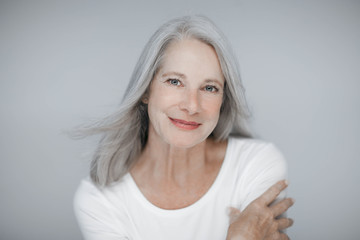 stunning beautiful and self confident best aged woman with grey hair smiling into camera Wall mural