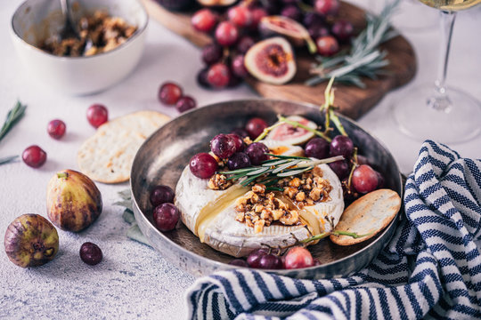 Fancy baked brie cheese platter with honey and walnuts, fresh rosemary. Red grapes, figs and white wine