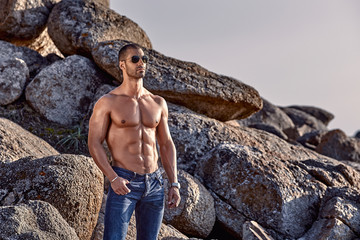 Muscular man with sunglasses close to the reef