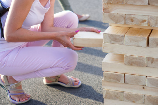 A girl in pink takes out one bar from the tower while playing a giant jenga. Outside