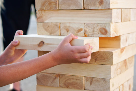 A child takes out one bar from the tower while playing a giant jenga. Outside