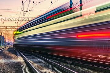 Fototapeta Passenger train moves fast at sunset time. obraz