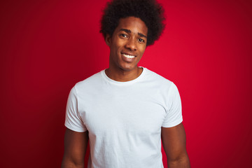 Young american man with afro hair wearing white t-shirt standing over isolated red background with a happy and cool smile on face. Lucky person. Fototapete