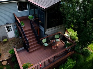 View of a landscaped back yard with a new composite deck and sunroom