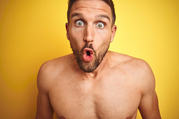Sexy young shirtless man showing nude fitness chest over yellow isolated background afraid and...