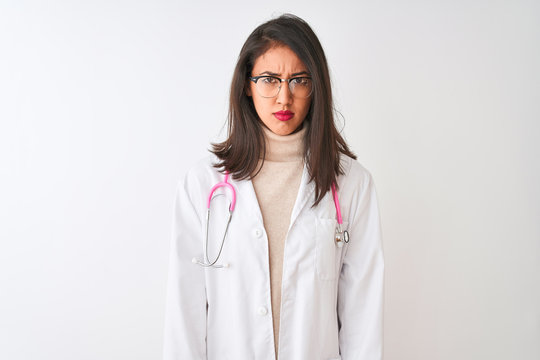 Chinese doctor woman wearing coat and pink stethoscope over isolated white background skeptic and nervous, frowning upset because of problem. Negative person.