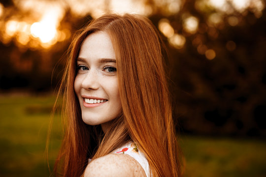 Close up portrait of a red hair woman girl with freckles looking at camera laughing over the shoulder against sunset outside.