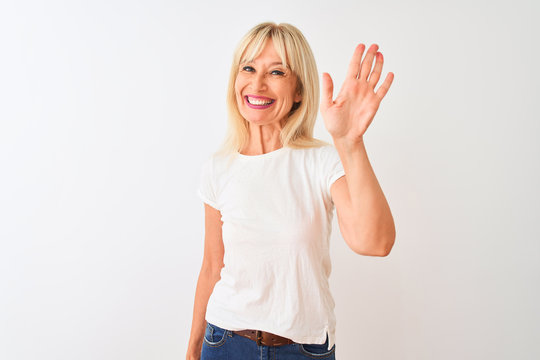 Middle age woman wearing casual t-shirt standing over isolated white background Waiving saying hello happy and smiling, friendly welcome gesture
