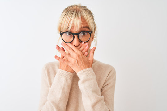 Middle age woman wearing turtleneck sweater and glasses over isolated white background shocked covering mouth with hands for mistake. Secret concept.