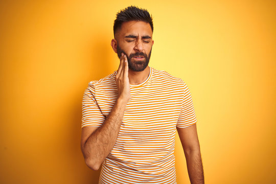 Young indian man wearing t-shirt standing over isolated yellow background touching mouth with hand with painful expression because of toothache or dental illness on teeth. Dentist concept.