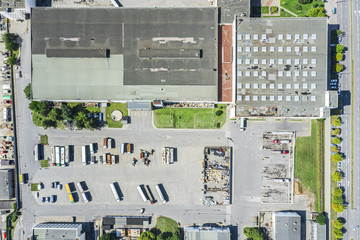 aerial top view of modern industrial building and warehouse with parked trucks and cars. drone photo