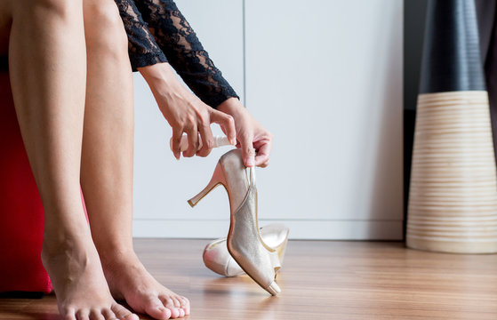 Woman hands using spray to high heel shoes because bad smell