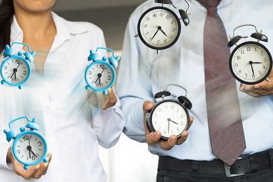 Office employees juggling with clock suggesting time management or stress at job