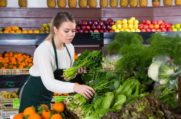 Female seller working with greens and letuce on the supermarket
