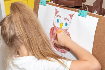 Little girl drawing owl on easel in class