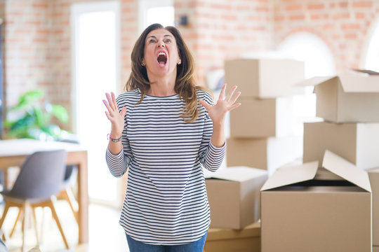 Middle age woman moving to a new house arround cardboard boxes crazy and mad shouting and yelling with aggressive expression and arms raised. Frustration concept.
