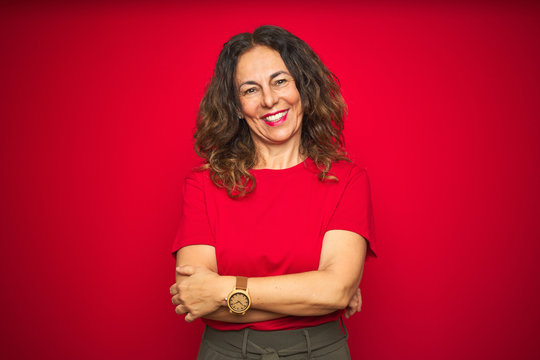 Middle age senior woman with curly hair over red isolated background happy face smiling with crossed arms looking at the camera. Positive person.