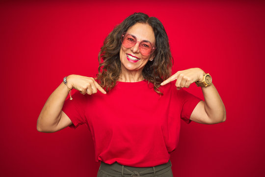 Middle age senior woman wearing cute heart shaped glasses over red isolated background looking confident with smile on face, pointing oneself with fingers proud and happy.