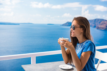 Wall Mural - Happy Asian woman drinking coffee enjoying summer vacation at luxury hotel cafe with amazing landscape view of Oia, Santorini. Europe travel destination. Tourist lifestyle.