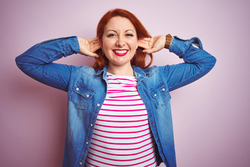 Beautiful redhead woman wearing denim shirt and striped t-shirt over isolated pink background Smiling pulling ears with fingers, funny gesture. Audition problem Wall mural