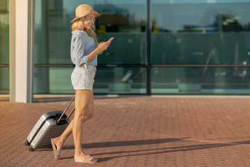 Young girl traveler walking with suitcase in the airport