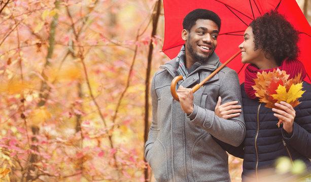 Autumn date. Loving couple walking under umbrella