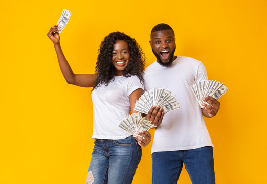 Excited black man and woman holding dollars