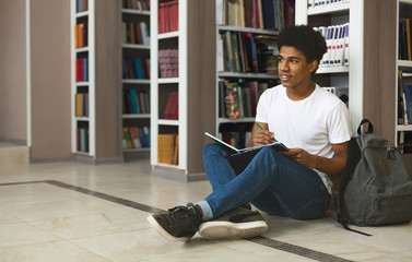 Creative afro student making notes, sitting on floor at library